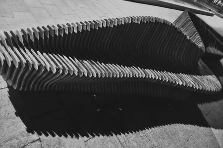 The spring creative wave pattern of a wooden slatted Bench on the coast.