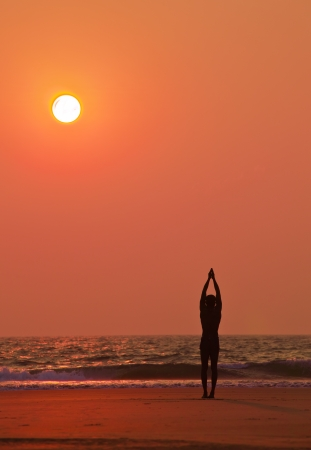 Yoga exercises at ocean sunset  Man s silhouette  photo