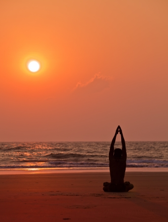 Yoga exercises at sunset  Man s silhouette  photo