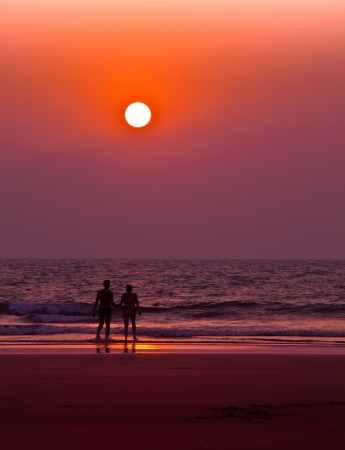 Couple on the beach in the sunset lignt photo