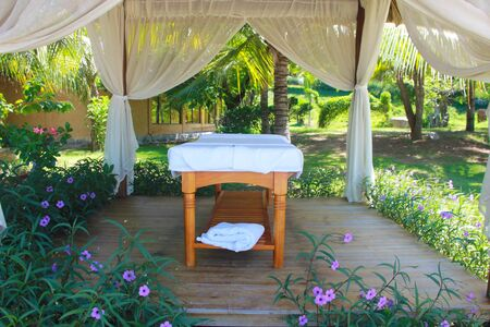 Spa tables at beachside in bungalow, massage tables with towels. Beauty care concept. Spa beds ready to massage at outdoors tropical island resort.