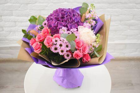 五颜六色的花美丽的花束在包装的在白色桌上反对砖白色墙壁背景。没有人。特写。花店的概念。编目的花束。
