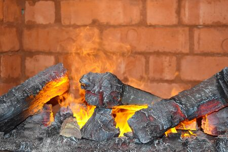The burning coals and firewood in a fireplace close up. A cozy interior of the house with fire.