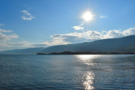 Picturesque natural water landscape. Beautiful mountain sunset on lake. Pearl of Siberia is Lake Baikal. Solar reflection in the water.