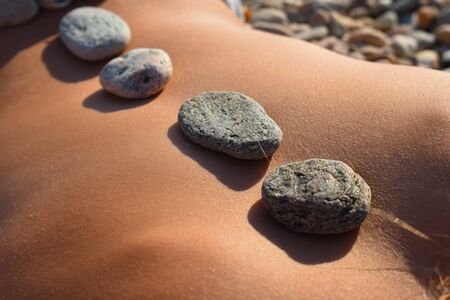 Natural hot stones on the back. Sea stone treatment. Stone therapy.