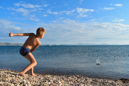 Boy in swimming trunks on  lake throws stones into  water. Teenager plays on seashore. Summer vacation with parents on lake on fresh air. Reklamní fotografie