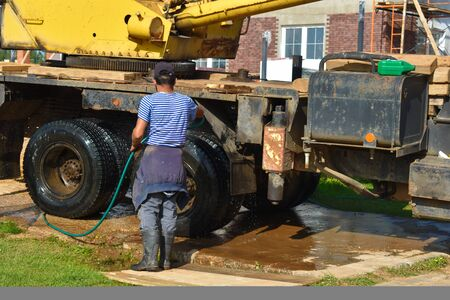 The hard work of a car washer. A worker is cleaning construction equipment. 写真素材