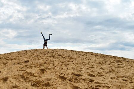 A girl plays on a big mountain of sand. Stock Photo
