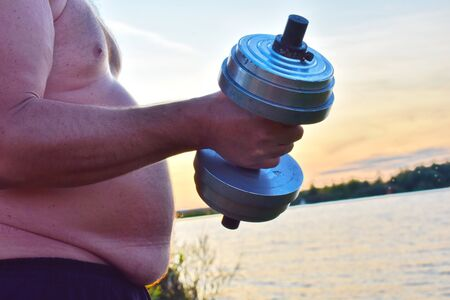 Fat man is engaged in weightlifting. Dumbbells for a fat man.