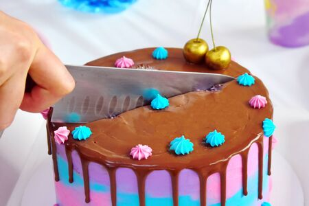 Hand with a knife cuts a colorful cake.