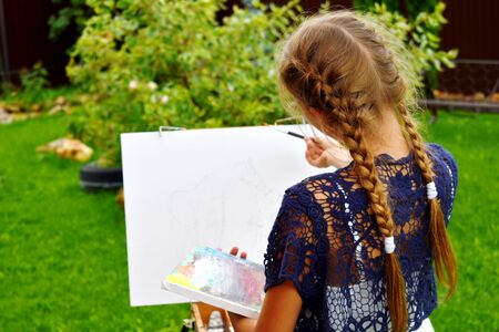 Drawing in the fresh air. Easel with a white canvas and a girl.
