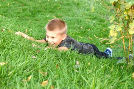 The boy crawls in the green grass in the summer. Cheerful happy summer vacation outdoor.