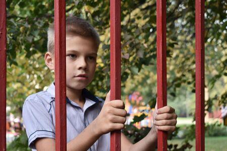 Un niño en cautiverio. Un adolescente mira a través de una valla enrejada. Orfanato. Lleva a un niño huérfano.