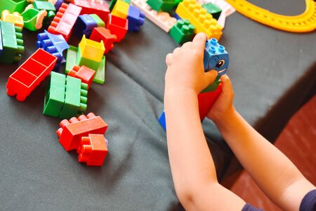 Childrens developmental constructor. A child builds a tower of colored cubes. 写真素材