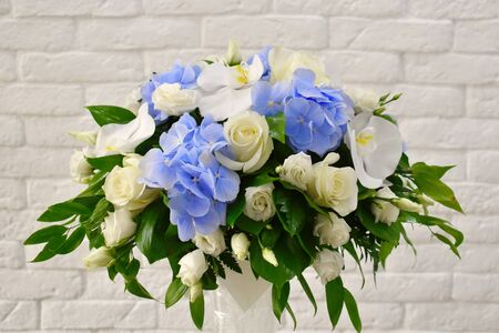 Blue hydrangea in a bouquet. Beautiful white bouquet for a wedding table.