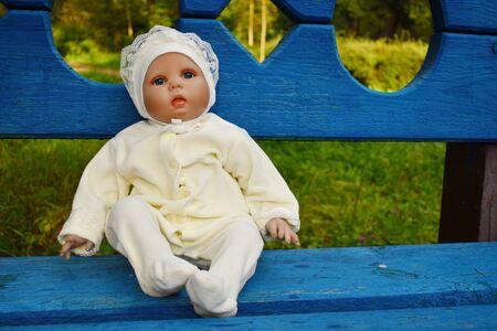 Schöne Puppe als lebendes Baby auf einer Außenbank. Lieblingsspielzeugmädchen.