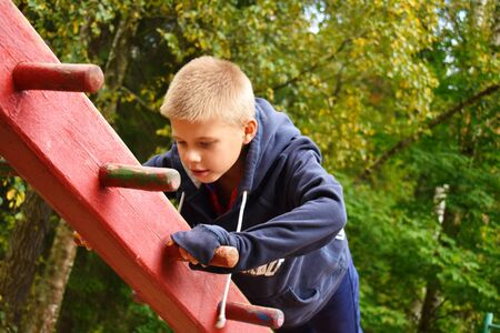 A boy on the playground goes in for sports. Training of children in the fresh air. Active childrens recreation outdoor.