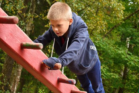 The boy climbs on a sports invernary in the fresh air. Sports school training.