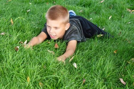 The child wallows in the green grass in the summer.