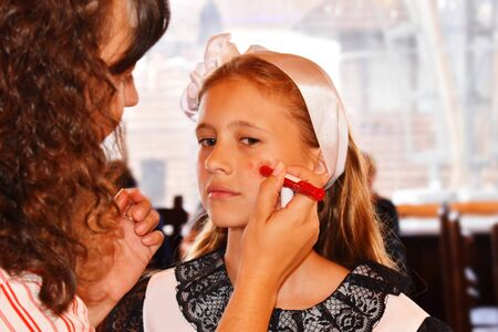 Preparing a model for a performance show. Making makeup on a teenage girl backstage.