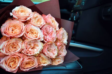 Delicate bouquet of peony roses. Home flower delivery. Beautiful roses in a car.
