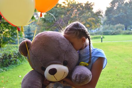 Teenagers problems at school. Failed spoiled holiday. Unhappy sad girl with a huge teddy bear in the summer.