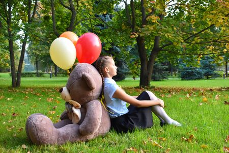 Schoolgirl unhappy in the park sitting on the grass with a big toy.Unhappy sad girl with a huge teddy bear