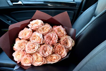 Valentine's day background. A bouquet of flowers in an expensive car. Standard-Bild