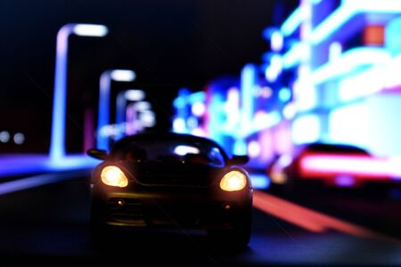 Collectible car model with headlights on. Night street with lights and a cool car. Abstract glowing background with a toy auto. Banque d'images - 133113768