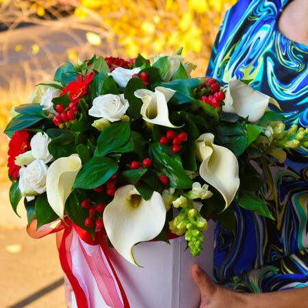 Romantic flowers for mothers day and womens day. The original bouquet in a hat box in the hands. A bouquet of flowers for the catalog of the flower salon. Stockfoto