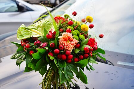 Spring flowers for the beloved. A blooming bouquet of flowers stands on the hood of a car. Original unusual wedding bouquet.