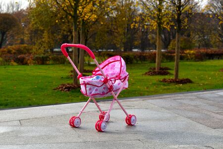 Toy carriage for dolls in a public park. Girl games in the fresh air. Stock Photo