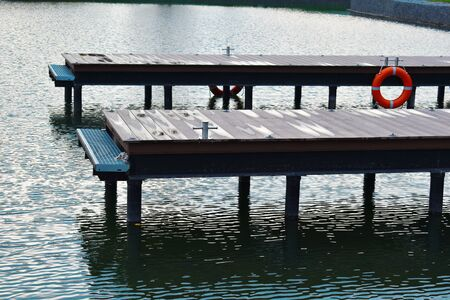 Lake in a city park with a wooden pier for boats. Cozy water natural landscape. A haven for small pleasure boats.