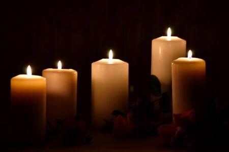 Brennende Kerzen und Rosen auf dunklem Hintergrund. Posthume brennende Kerzen. Trauerbild mit Platz für Text. Standard-Bild