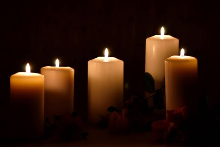 Burning candles and roses on a dark background. Posthumous burning candles. Mourning picture with place for text. Stock Photo