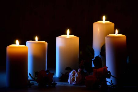 Burning candles and roses on a dark background. Posthumous burning candles. Mourning picture with place for text.