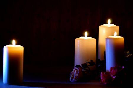Brennende Kerzen und Rosen auf dunklem Hintergrund. Posthume brennende Kerzen. Trauerbild mit Platz für Text.