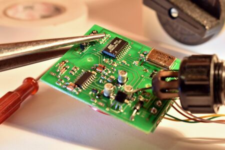 The electric chip is repaired with a soldering iron. Repair of household appliances. Digital integrated microelectronic device.