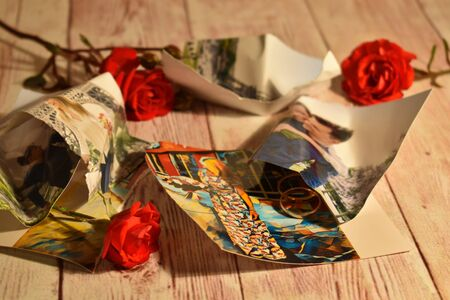 The concept of unhappy love. Separation, severed relationship. Problems in love and family. Flower and crumpled photo