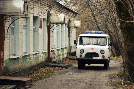 Antiguo hospital ruinoso y una antigua ambulancia. Foto de archivo
