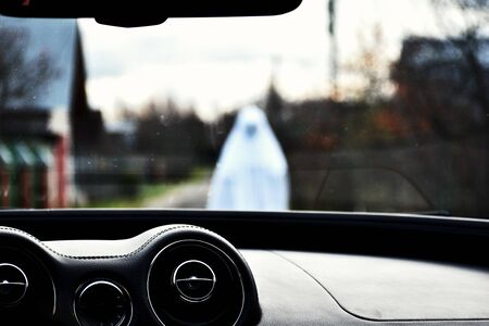 Otherworldly creature scares people on the track. Restless soul walks. Phantom of  dead man in white clothes.