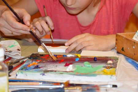 Drawing paints with teacher. Artist's tools. Art school. Child with art brush paints picture.