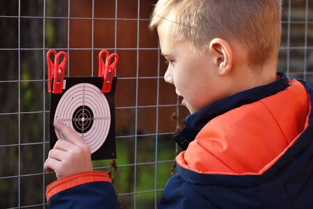Child and shooting target. Boy learns to shoot and hit target. Boy war games. Shooting sport. 版權商用圖片