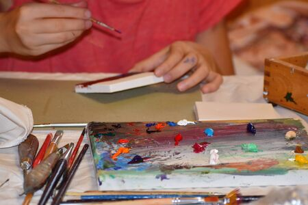 The child draws with oil paints. Artists tools on the table. Art studio.
