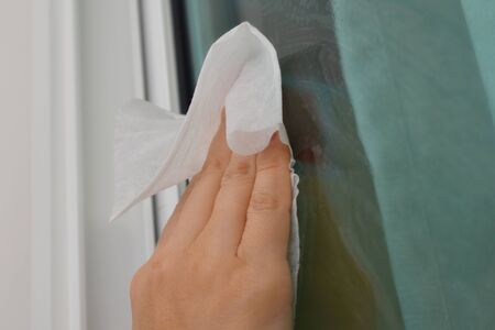 Wipe the window with a rag. Cleaning the house.