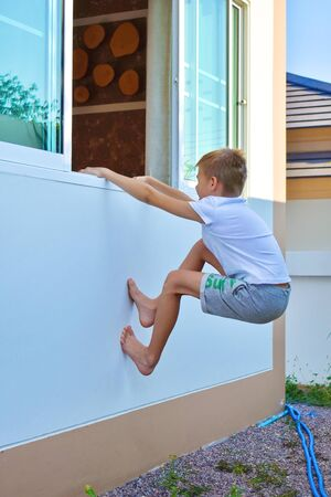 Boy teen climbs out the window home. Active children's leisure in the summer. funny kids games outdoor. Hide and seek Reklamní fotografie