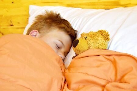 Boy sleeps with a Teddy bear. Children's healthy sleep. Archivio Fotografico
