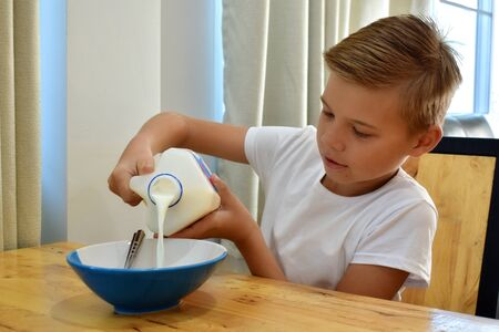 Boy eating cornflakes with milk. A healthy childrens breakfast.