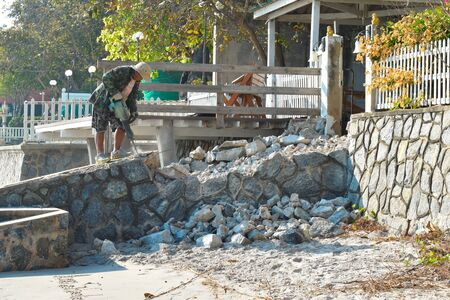 Thailand. Hua hin. January 2020. Repair work on beach. Worker with a jackhammer. Device is hollow stone. Jackhammer for rock. Redactioneel