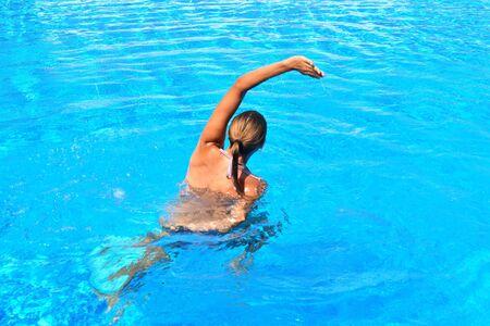Esercizio in piscina. Ragazza che fa esercizi ginnici in acqua. Sport acquatici attivi. L'Aquafitness per le donne. Archivio Fotografico